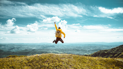 Obraz Hiker with backpack raising hands jumping on the top of a mountain - Successful man with arms up enjoying victory - Sport and success concept  - fototapety do salonu