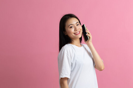 Smiling asian woman speaking mobile phone standing on pink background