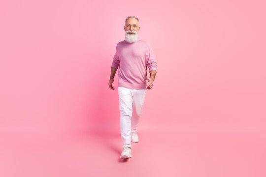 Photo of pretty adorable age gentleman wear sweater spectacles walking smiling isolated pink color background