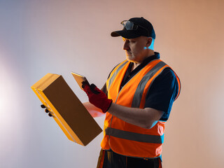 Fototapeta Order fulfillment process concept. A man works in an order fulfillment center. He photographs a cardboard box with his phone. An employee of an order fulfillment center in an orange vest. obraz