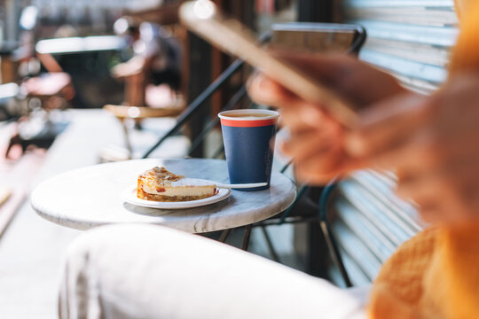 Paper cup with coffee and piece of cheesecake on table in outdoor cafe on background of blurred young woman with the mobile phon