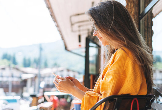 Young woman with long blonde hair wearing sunglasses and yellow longsleeve with mobile phone in hands in cafe, city life