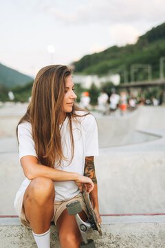 Slim young woman with long blonde hair in light sports clothes sitting with longboard in the outdoor skatepark at sunset
