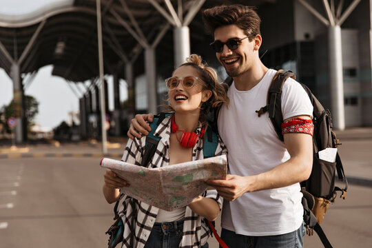 Young joyful woman and brunette man hug and holds map. Travelers decide where to go. Guy and girl in white t-shirts smiles and holds backpacks.