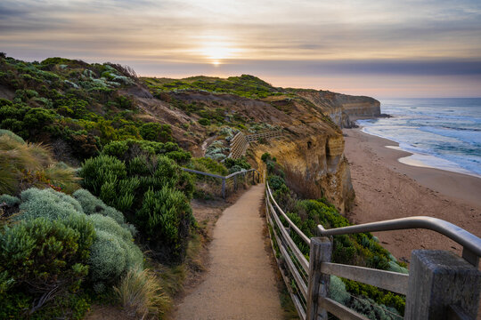 Looking down coastal walking track towards the sunrise and the beach below