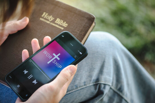 Women holding mobile phone praying worship to God with church online with the bible.Quarantine from Covid-19 Coronavirus pandemic, Online church from home concept.