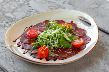 Beef carpaccio with arugula and parmesan on gray surface