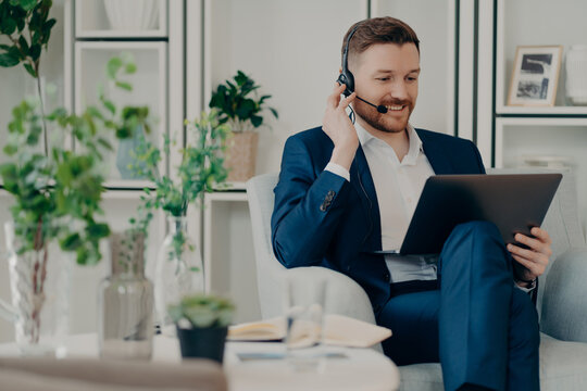 Freelance workday. Cheerful busy man manager works distantly from home online makes video call via laptop computer and headphones discuss working issues with business partner analyzes statistics