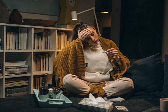 woman has flu, she measures temperature