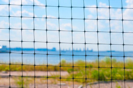 Blurred landscape with river and blue sky through the bars of the gate