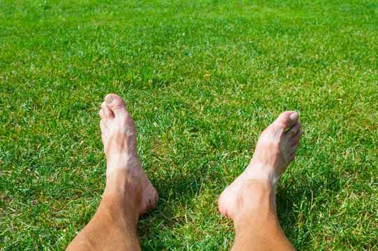 Tanned bare men's feet on a green grass