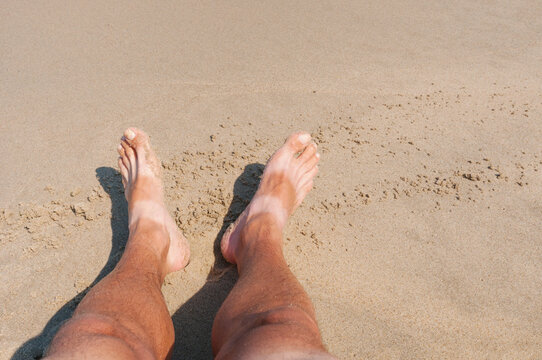 Tanned bare men's feet on  sand of a beach