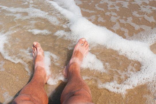 Tanned bare men's feet on  a sea coast