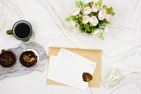 flat lay wedding card envelope and coffee cup with macarons and bouquet of flower's in bed