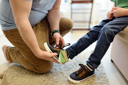 Online shopping for baby and kids. Father helping fitting shoes for his child at home. Free of charge courier delivery from online store of children's goods.