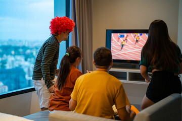 Obraz Group of Asian people friends sit on sofa watching and cheering sports games competition on TV together at home. Excited man and woman sport fans celebrate sport team victory in national sports match - fototapety do salonu