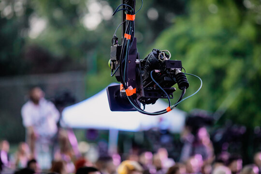 Shallow depth of field (selective focus) image with a professional video camera on a crane during an outdoor event.