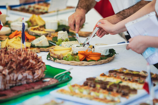 Shallow depth of field (selective focus) image with people eating french cuisine aperitifs from a table.