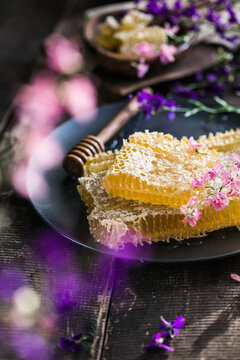 honeycombs with full cells of honey sealed with wax on wooden table on background honeycombs