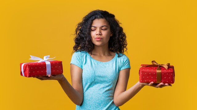 Pensive dark skinned girl holding two gift boxes in both hands deciding which one to choose