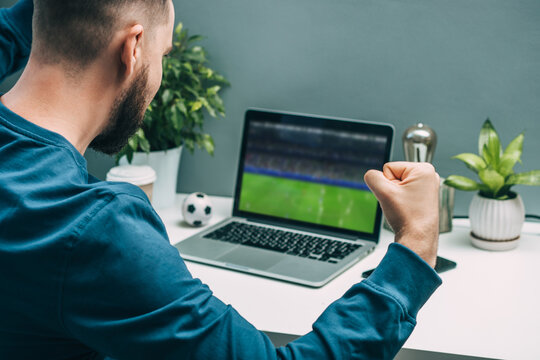 Over the shoulder view of euphoric young man watching soccer play live broadcast on his laptop and cheering for favourite team