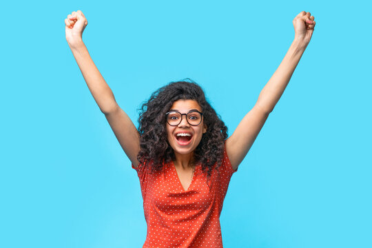 Portrait of happy excited girl making winner's gesture clenching her fists and holding hands up