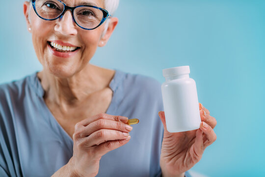 Supplements. Senior woman holding capsule and a blank white supplement container.