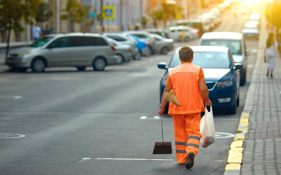 Municipal worker clean up street in the evening. worker in orange uniform collecting garbage from road and sidewalk. Woman in orange uniform with broomstick and scoop for garbage sweep city street