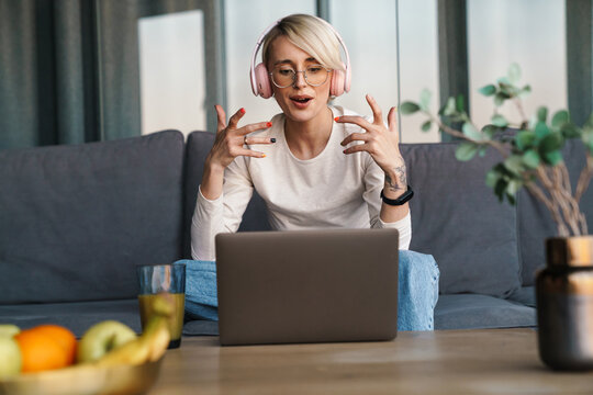 Smiling mod aged blonde woman studying online