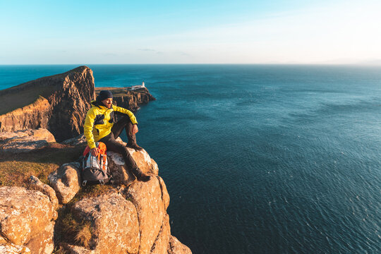 Man sitting on top of a cliff in Scotland