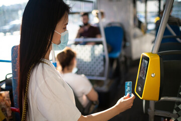Asian woman paying conctactless with plastic card for the public transport in bus, tram or subway...