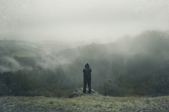 A lone hooded figure on top of a hill, looking out across the countryside on a foggy, rainy winters day. With a deliberate grunge, grainy, muted edit.