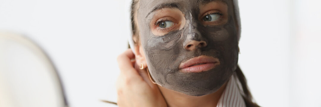 Young woman makes rejuvenating clay face mask