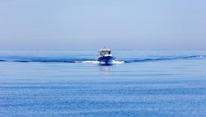 Obraz Greece. Aegean sea. Boat cruising. Blue sky and calm sea water background - fototapety do salonu
