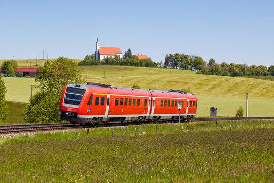 Bombardier Transportation RegioSwinger regional train Deutsche Bahn DB in Aitrang Bavaria with St. Alban church in Germany