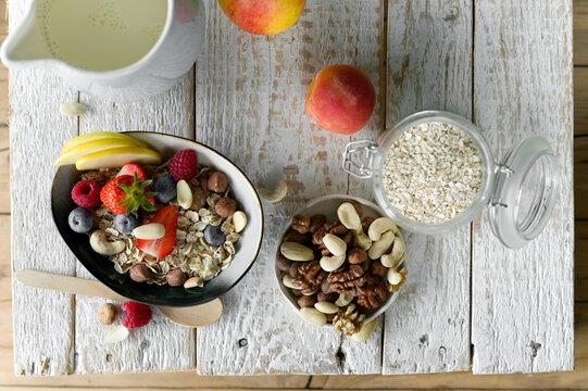 Healthy breakfast: muesli, fruit, milk on rustic wooden tray