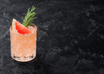 Fototapeta Grapefruit and rosemary drink, alcohol or non-alcohol cocktail in glass with ice cubes on black background. obraz