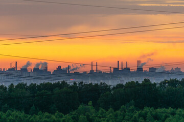 Smoking chimneys at dawn. Forest, industrial landscape and wires. The border of nature and civilization.