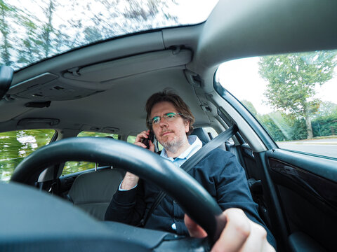 Low angle on a Caucasian male with glasses holding the wheel wearing seatbelt talking with phone