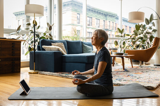 Senior woman meditating while learning through digital tablet in living room at home