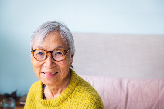 Smiling senior woman wearing yellow sweater sitting in bedroom at home