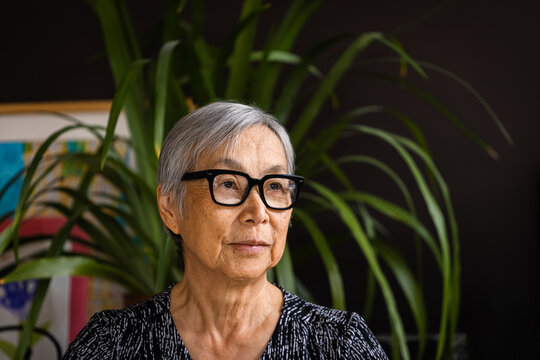 Portrait of Senior Woman wearing glasses at home with plants