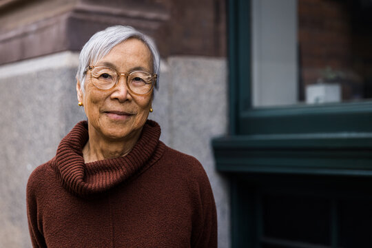 Portrait of smiling senior woman wearing glasses in the city