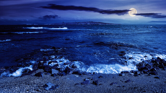 seascape at night. wonderful scenery with islands in full moon light. clouds above horizon. fantasy travel destination in summer