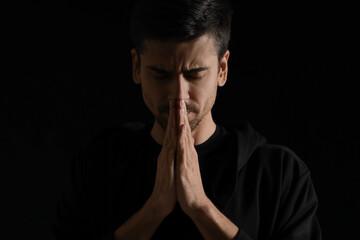 Obraz Religious young man praying on dark background - fototapety do salonu