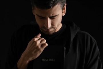 Obraz Religious young man with Bible praying on dark background - fototapety do salonu