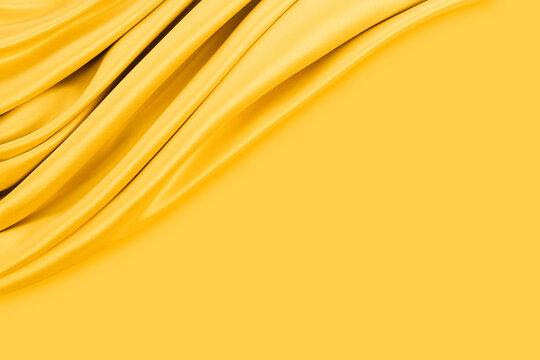 Beautiful elegant wavy yellow satin silk luxury cloth fabric texture with monochrome background design. Copy space