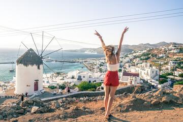 Fototapeta kobieta z widokiem na greckie miasto i wiatrak obraz