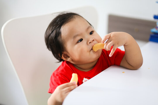 Adorable Asian baby girl sitting on the chair and eating snack.