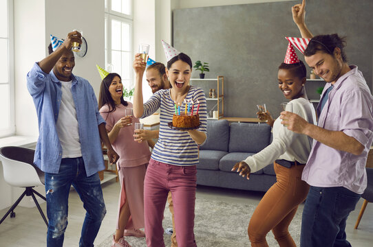 Diverse multiracial group of happy people in funny hats dancing and having fun at casual birthday party at home. Cheerful young woman holding cake with lit candles dancing surrounded by best friends